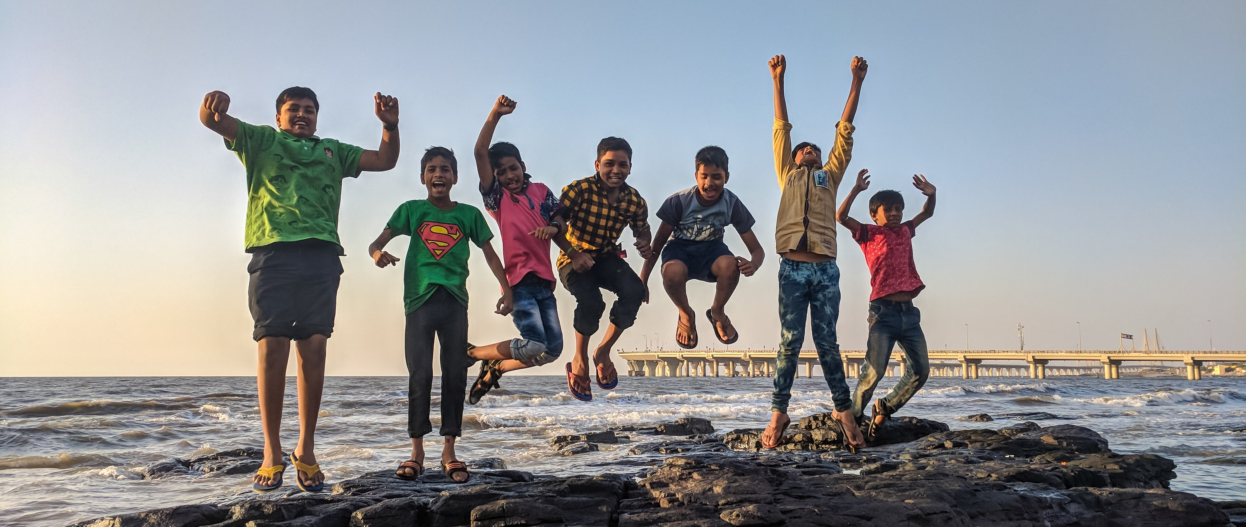 Group of children jumping and celebrating by the ocean